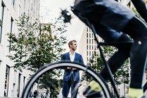 Ciclista en la calle en la ciudad con el empresario sobre fondo - foto de stock