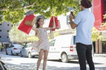 Young woman holding shopping bags in arms raised posing for photo taking by boyfriend — Stock Photo