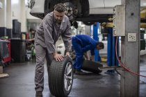 Car mechanics in a workshop changing tires — Stock Photo