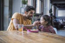 Père, fille d'alimentation avec des fruits assis à la table de la cuisine — Photo de stock