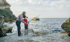 Дідусь і онук, Риболовля разом на море — стокове фото