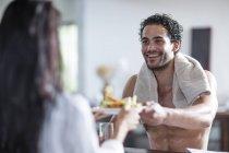 Sorridente giovane coppia a casa mangiare panini — Foto stock