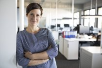 Portrait of confident businesswoman standing with arms crossed in office — Stock Photo