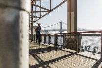 USA, New York City, homme courant à East River sous Brooklyn Bridge — Photo de stock