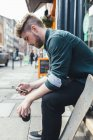 Jovem homem com skate, celular e xícara de café sentado no banco em Dublin, Irlanda — Fotografia de Stock