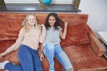 Due ragazze felici rilassarsi sul divano e guardando la fotocamera — Foto stock