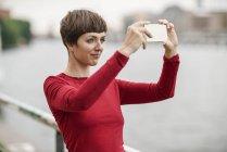 Портрет молодой женщины принимая selfie с смартфон — стоковое фото