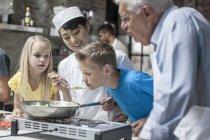 Chef instructor permite niño el olor de la olla - foto de stock