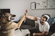 Young man and dog high fiving indoors — Stock Photo