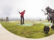 Italy, Veneto, Dolomites, golfer on green golf course in cloudy weather — Stock Photo