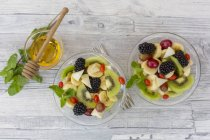 Fruit salad with blackberries in bowls on wooden surface — Stock Photo