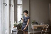 Junge Frau benutzt Smartphone und Kopfhörer zu Hause — Stockfoto