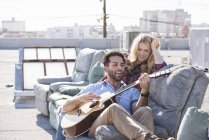 Man playing guitar to woman sitting on couch at rooftop party, Los Angeles, USA — Stock Photo