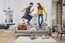 Retrato de pareja saltando en sofá en tienda de muebles - foto de stock
