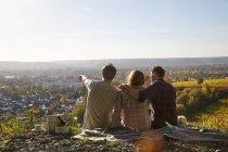 Amis assis sur une colline au-dessus d'une ville — Photo de stock