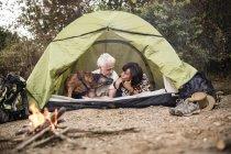 Старший пара з собакою лежав у наметі на багаття — стокове фото