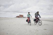 Casal andar de bicicleta na praia com céu nublado no fundo — Fotografia de Stock