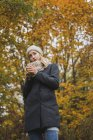 Young woman with hot beverage standing in autumn forest — Stock Photo