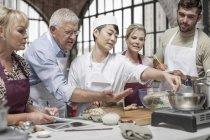 Взрослых Добавление специй, а шеф-повар инструктирует их в кулинарии — стоковое фото
