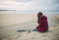 Mujer joven en la playa en busca de su teléfono inteligente - foto de stock