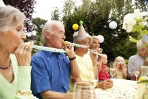 Extended family and friends having birthday party in garden — Stock Photo