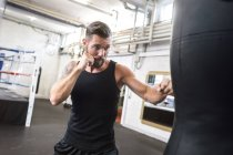 Caucasian boxer exercising at punch bag — Stock Photo