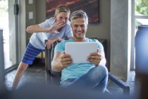 Father and son looking at digital tablet,having fun and games — Stock Photo