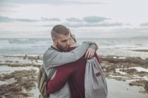 Young gay couple with backpacks hugging on the beach — Stock Photo