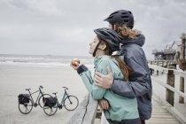 Pärchen auf Fahrradtour macht Pause am Steg am Strand — Stockfoto