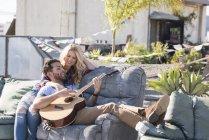 Paar auf dem Dach sitzt auf Sofa und spielt Gitarre — Stockfoto