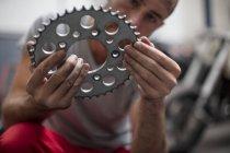 Nahaufnahme der Mechaniker mit einem Kettenrad in Werkstatt — Stockfoto