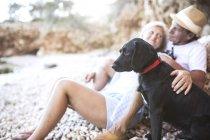 Activo Linda senior pareja relajante en la playa con perro - foto de stock