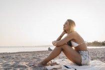 Jovem mulher sentada no cobertor no crepúsculo beachat — Fotografia de Stock