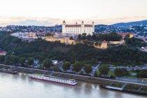 Vista de Eslovaquia, Bratislava, al castillo con el río crucero por el Danubio en primer plano en el crepúsculo - foto de stock