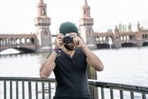 Germany, Berlin, man standing in front of Oberbaum taking pictures from viewer — Stock Photo