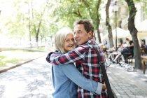 Vue latérale de l'heureux couple de personnes âgées mignon étreignant les uns les autres — Photo de stock