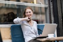 Cute redhead caucasian woman using laptop at cafe — Stock Photo