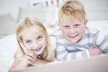 Portait of smiling brother and sister lying in bed with laptop — Stock Photo