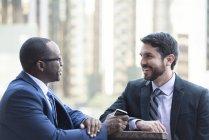 Zwei Lächelnde Geschäftsleute sprechen im freien — Stockfoto