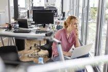 Mujer con el portátil en la oficina mirando por la ventana - foto de stock