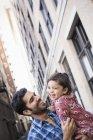 Батько тримає свою дочку малюка під час прогулянки по вулиці міста — стокове фото