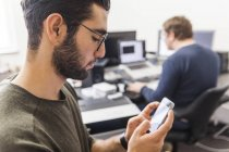 Jovem, usando o smartphone em um escritório moderno com colega de trabalho no fundo — Fotografia de Stock