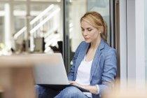 Kaukasische blonde Frau mit Laptop im Büro — Stockfoto