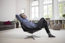 Relaxed mature man sitting in chair at modern home — Stock Photo