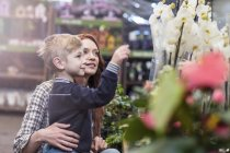 Mother and son at garden centre by flowering plants — Stock Photo