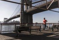 Estados Unidos, Nueva York, hombre corriendo en East River bajo el puente de Brooklyn - foto de stock
