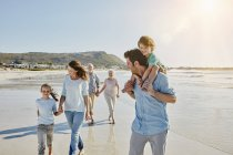 Portrait of three generations family strolling on beach — Stock Photo