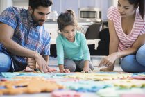 Happy family sitting on floor and playing with daughter — Stock Photo