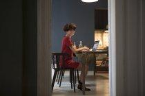 Giovane donna sorridente seduto in cucina e l'utilizzo del computer portatile — Foto stock