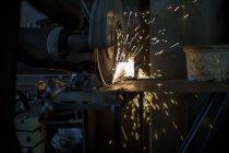 Nahaufnahme des Mechanikers mit dem Tischschleifer in der Werkstatt — Stockfoto